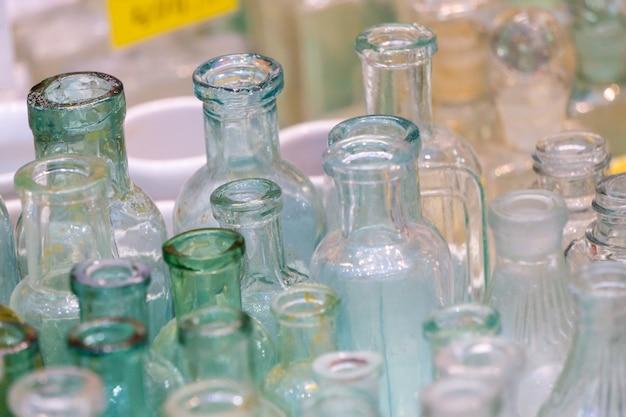 Muitas garrafas de vidro vazias de diferentes formas e cores