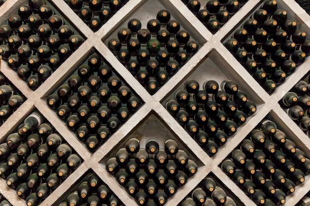 Muitas garrafas de vinho empoeiradas estão nas prateleiras, prateleiras de garrafas de vinho