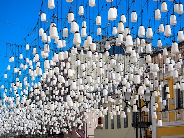 Muitas lâmpadas brancas penduradas na rua. iluminação e decoração de rua.