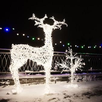 Muitas lâmpadas de luzes festivas em forma de veado na iluminação festiva de noite à noite. elementos decorativos de ruas na temporada de férias de natal