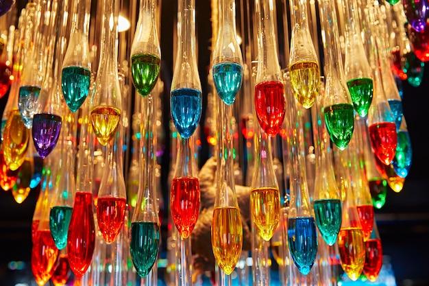 Muitas lâmpadas multicoloridas em forma de gotas estão penduradas no teto
