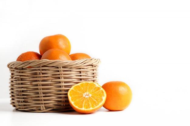 Muitas laranjas frescas em uma cesta de madeira colocada no chão.