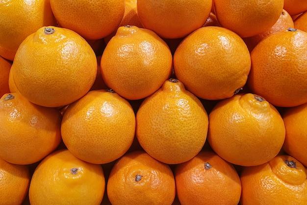 Muitas laranjas suculentas e brilhantes depositadas exatamente em uma pilha em uma loja no mercado