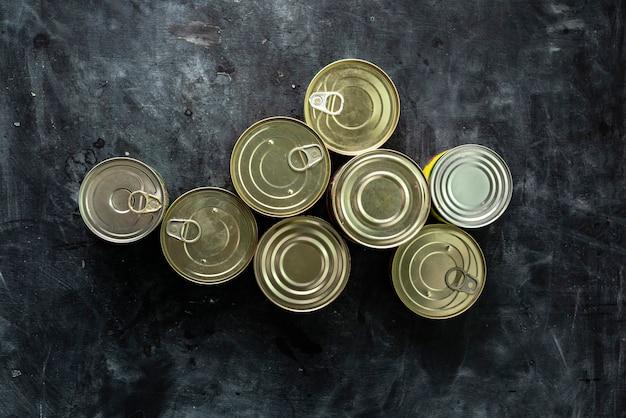 Muitas latas fechadas com refeições, como carne e peixe na mesa, alimentos conservados
