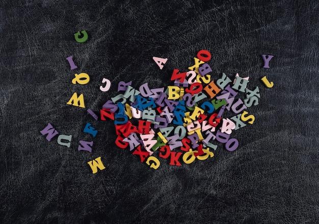 Muitas letras coloridas em um fundo de quadro de giz. de volta à escola. vista do topo.