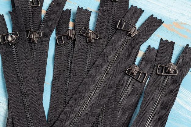 Muitas listras de zíper de metal preto com controles deslizantes para costura artesanal, alfaiataria.