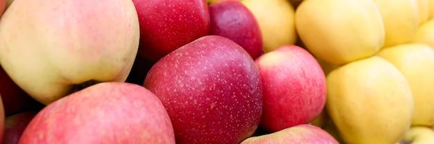 Muitas maçãs amarelas e vermelhas no balcão do close up da loja
