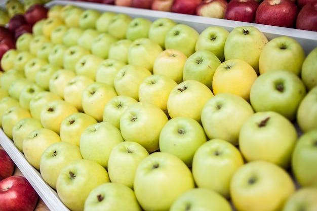Muitas maçãs verdes lindamente dispostas no mercado ao vento