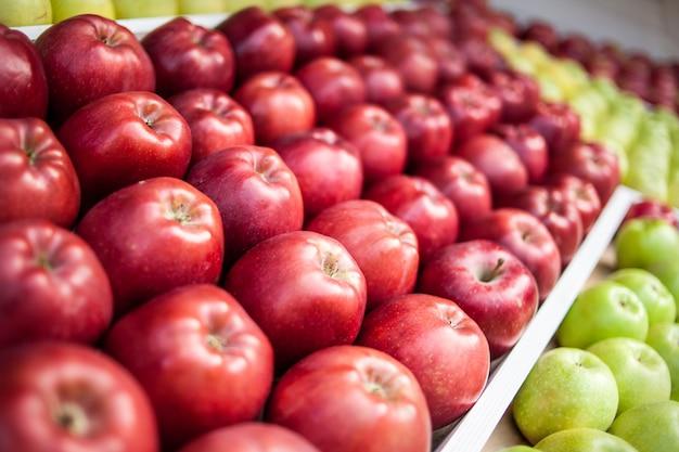 Muitas maçãs vermelhas lindamente estabelecidas no mercado no vento