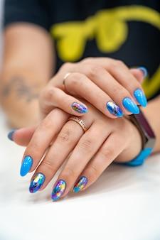 Muitas mãos de manicure com brilho colorido têm manchas diferentes em uma luz