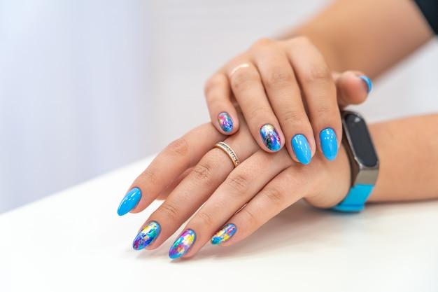 Muitas mãos de manicure com brilho colorido têm manchas diferentes