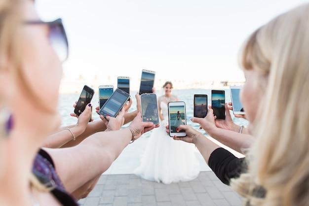 Muitas mãos femininas com telefones inteligentes fazendo fotos