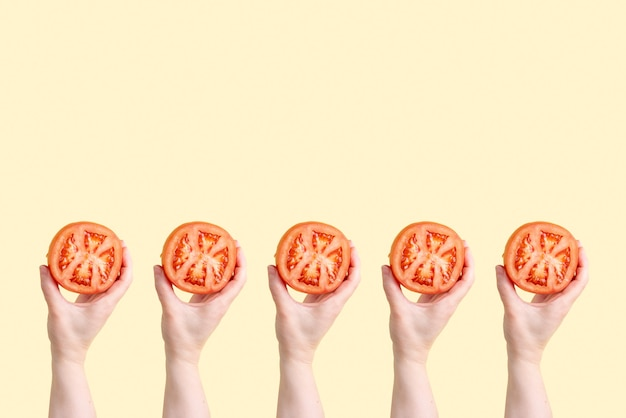 Muitas mãos femininas com tomates