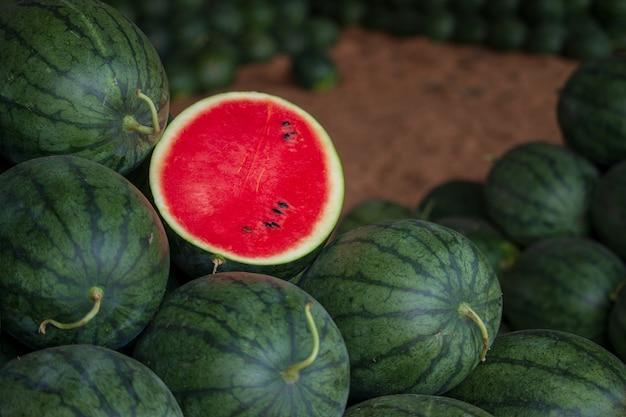 Muitas melancias verdes doces grandes e uma melancia cortada