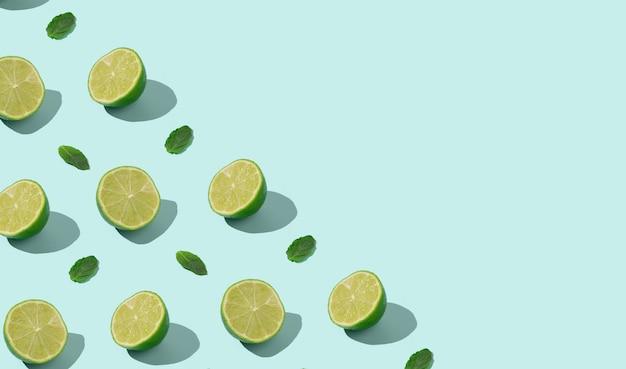 Muitas metades de limão e folhas de hortelã armação de borda em fundo ciano pastel com espaço de cópia