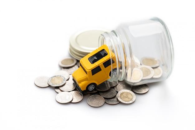 Muitas moedas em uma jarra de vidro e um carro de brinquedo amarelo