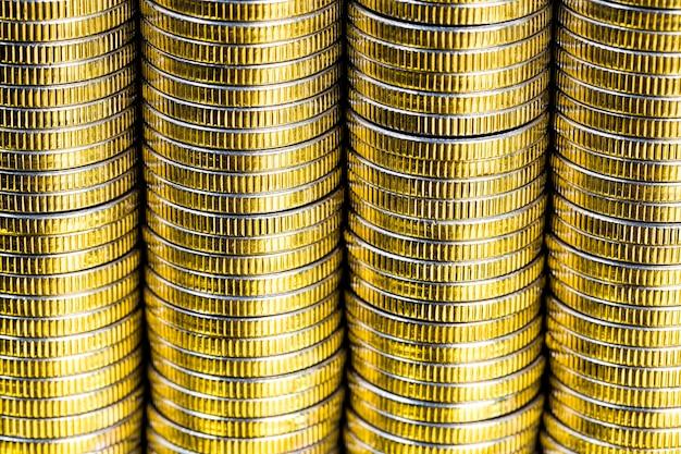 Muitas moedas redondas de metal de cor prata iluminadas em amarelo, curso legal usado para pagamentos no estado, belas moedas em close-up em um matiz amarelo do mesmo valor