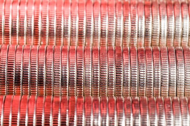 Muitas moedas redondas de metal de cor prata iluminadas em vermelho, curso legal usado para pagamentos no estado, belas moedas em close com um matiz vermelho do mesmo valor