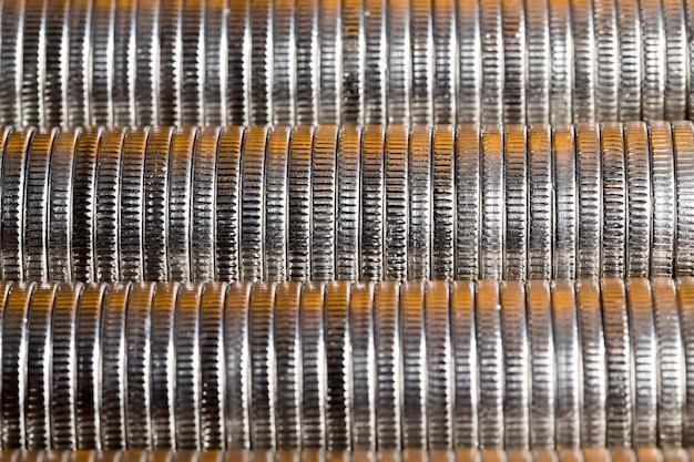 Muitas moedas redondas de metal prateado iluminadas com a cor dourada, moeda corrente usada para pagamentos no estado, lindas moedas em close-up com tonalidade dourada do mesmo valor