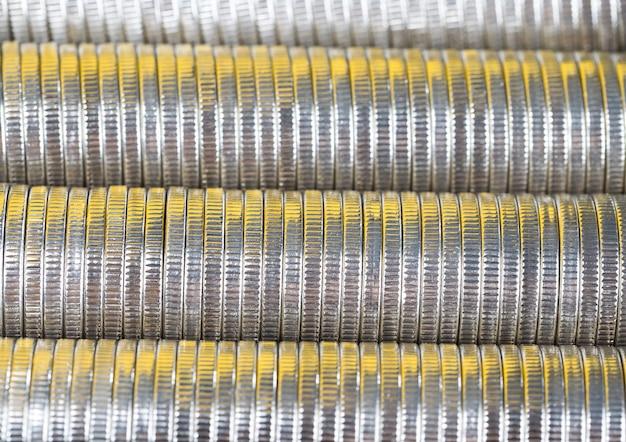 Muitas moedas redondas de metal prateado iluminadas em amarelo, moeda corrente usada para pagamentos no estado, lindas moedas em close-up com tonalidade amarela do mesmo valor
