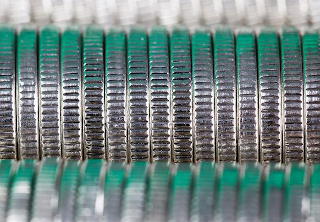 Muitas moedas redondas de metal prateado iluminadas em verde, curso legal usado para pagamentos no estado, belas moedas em close-up em tom verde com o mesmo valor