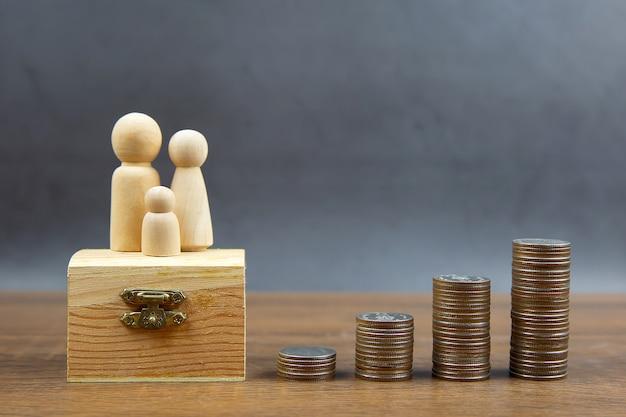 Muitas moedas são empilhadas em forma de gráfico com a boneca de madeira da família para idéias de economia de dinheiro.