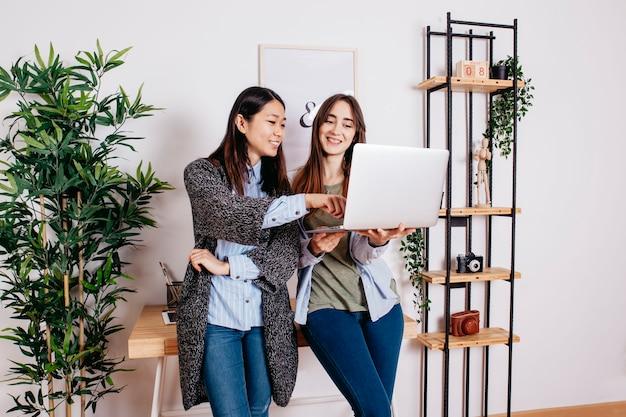 Muitas mulheres multirraciais que trabalham no laptop