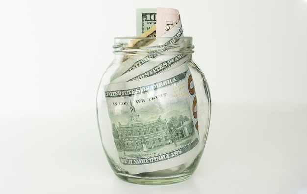 Muitas notas de 100 dólares americanos em um frasco de vidro isolado no branco