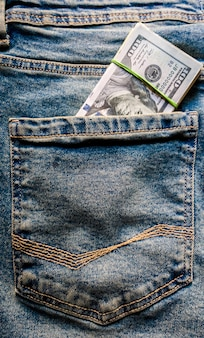 Muitas notas de cem dólares no bolso da calça jeans. os dólares americanos ficam visíveis no seu bolso. riqueza nas calças. posição vertical da foto.