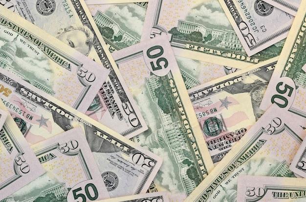 Muitas notas de cinquenta dólares dos eua na superfície plana close-up. vista superior plana leiga. conceito abstrato de negócios