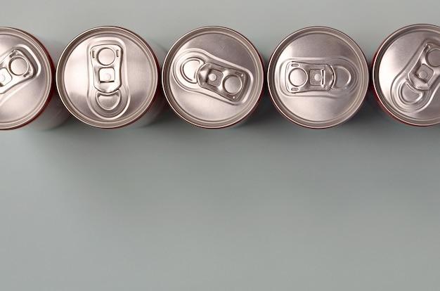 Muitas novas latas de alumínio de refrigerantes ou recipientes para bebidas energéticas. conceito de fabricação de bebidas e produção em massa