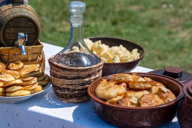 Muitas panquecas, bolinhos e vinho na mesa no quintal, close-up, ucrânia. comida tradicional ucraniana