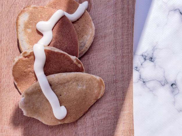 Muitas panquecas deliciosas e apetitosas com creme de leite em uma placa de madeira