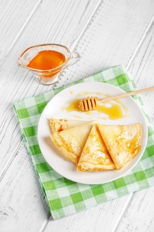 Muitas panquecas doces com mel. o conceito de comida, café da manhã,