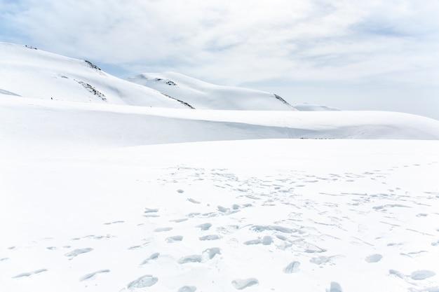Muitas pegadas na montanha coberta de neve