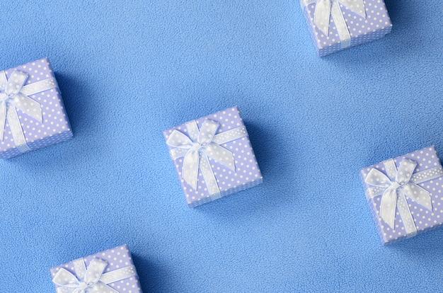 Muitas pequenas caixas de presente na cor azul com um pequeno arco encontra-se em um cobertor