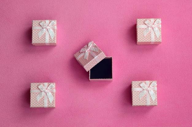 Muitas pequenas caixas de presente na cor rosa com um pequeno arco encontra-se em um cobertor