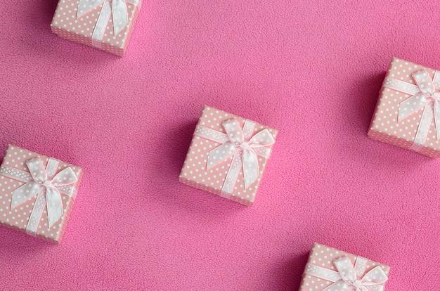 Muitas pequenas caixas de presente na cor rosa com um pequeno arco