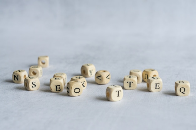 Muitas pequenas letras de madeira no fundo cinza