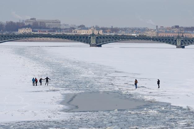 Muitas pessoas atravessando o rio neva congelado em são petersburgo no início da primavera