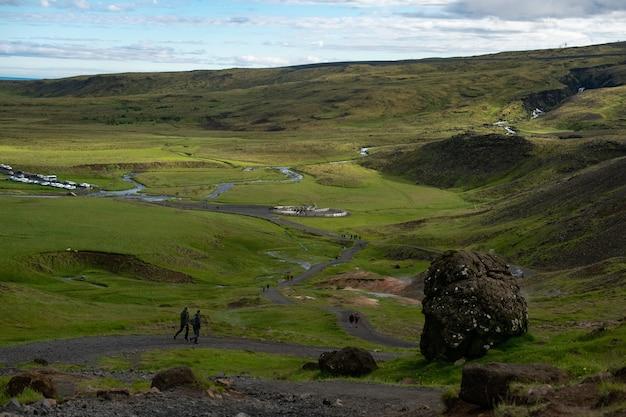 Muitas pessoas caminhando por um caminho estreito em um terreno verde cercado por colinas verdes