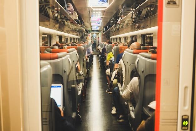 Muitas pessoas se sentam em um metrô no trem indo para destinos a trabalho ou lazer, como férias. internet wi-fi moderno conectado durante a viagem
