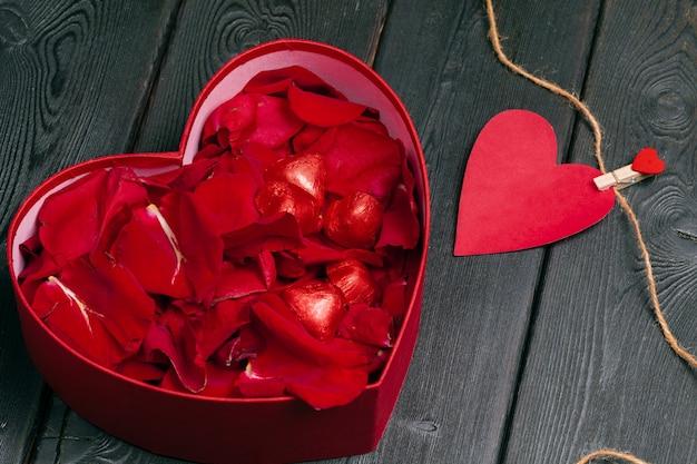 Muitas pétalas de rosa dentro da caixa de presente aberta