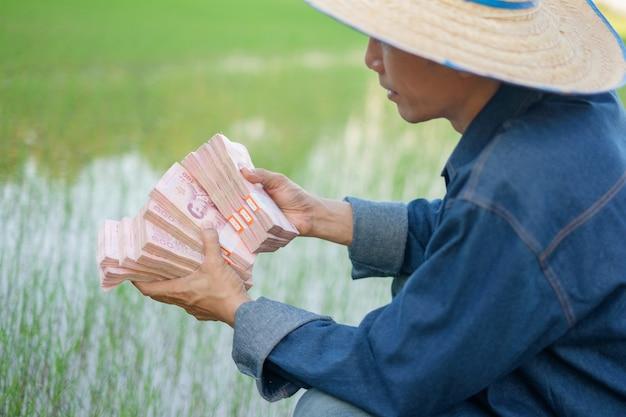 Muitas pilhas de dinheiro das notas tailandesas na mão do fazendeiro na fazenda verde. imagem de foco seletivo.