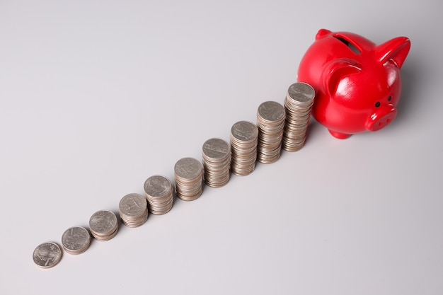 Muitas pilhas de moedas e um cofrinho de porco vermelho na mesa investindo economias financeiras lucrativas