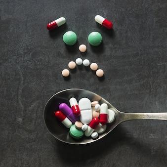 Muitas pílulas coloridas e guias com colher em um fundo escuro