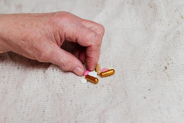 Muitas pílulas diferentes na mão de uma pessoa idosa.