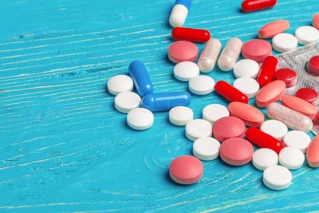 Muitas pílulas diferentes na mesa de madeira azul escura
