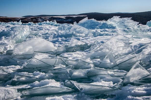 Muitas placas de gelo afiadas e finas em um grande monte de neve no lago baikal
