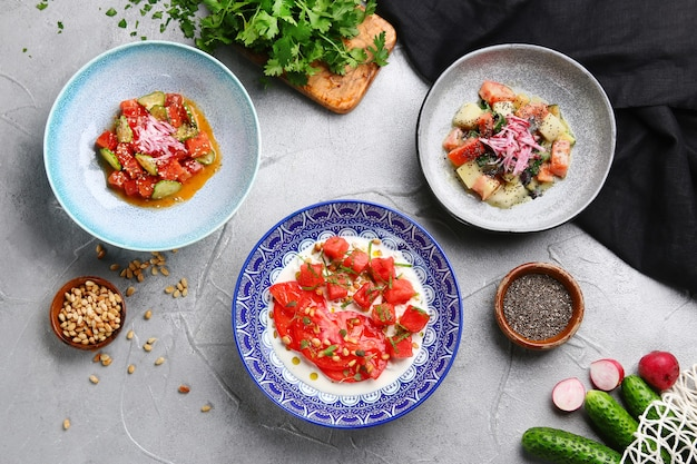 Muitas salada na mesa de concreto leve competem. ceviche com atum, salmão e stracciatella com tomate e salada de melona.